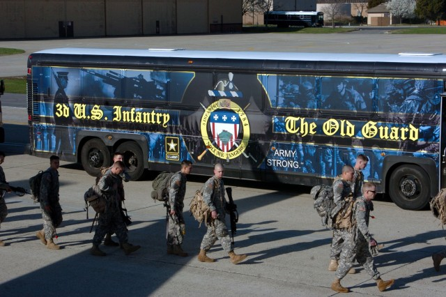 Soldiers from H Co., 1st Battalion, 3rd U.S. Infantry Regiment (The Old Guard) walk along one of The Old Guard buses headed to board an airplane that will take them to train at the Joint Readiness Training Center at Fort Polk, La.