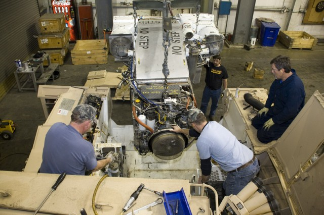 Anniston Army Depot, Ala., mechanics use the help of an overhead crane to insert an overhauled AGT 1500 turbine engine into an M1 tank.