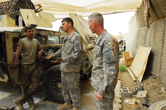 BAGHDAD - Mechanics Staff Sgt. Denis Mcfall, who hails from Point Pleasant, W. Va. and Marietta, Ohio native, Sgt. Robert Knotts, both from Company E, 1st Battalion, 505th Parachute Infantry Regiment, discuss vehicle maintenance with Iraqi Army mechanic Sgt. Jasim Malik from the 1st Battalion, 55th Brigade, 17th IA Division at Joint Security Station Zubaida March 28.