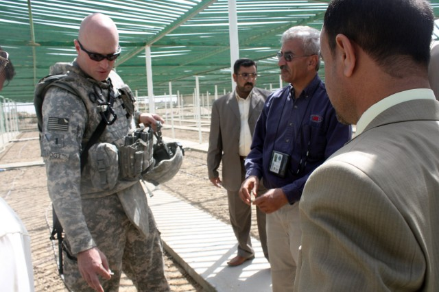 1st Lt. Devens Vogt, a civil capacity officer for 14th Engineer Battalion, guides local Dhi Qar politicians and Provincial Council members on a tour of the Nasiriyah Tree Nursery during its opening ceremony March 26. The nursery has two greenhouses and a fenced-off area for growing trees.