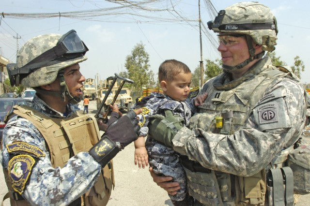 BAGHDAD -Capt. Clay White, of Williamsburg, Va., commander of Company C, 2nd Battalion, 505th Parachute Infantry Regiment, 3rd Brigade Combat Team, 82nd Airborne Division, talks to a National Police officer as he carries an Iraqi child wearing a NP uniform following a distribution event in the area of Sumer al-Ghadier April 1 in the 9 Nissan district of eastern Baghdad. White and his Paratroopers were invited by district officials to participate in the event in honor of National Orphan Day.