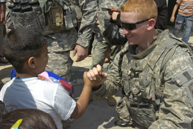BAGHDAD - 1st Lt. Phillip Turner, of Elizabethtown, Ky., greets an Iraqi child during a distribution event April 1 in the area of Sumer al-Ghadier, located in the 9 Nissan district of eastern Baghdad. Turner and Paratroopers assigned to the Company C, 2nd Battalion, 505th Parachute Infantry Regiment, 3rd Brigade Combat Team, 82nd Airborne Division, Multi-National Division - Baghdad were invited by district officials to a local school in order to participate in National Orphan Day. District officials and Iraqi Security Forces handed out clothes and school supplies to more than 60 orphan children during the event.