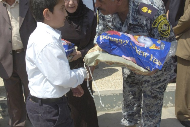 BAGHDAD - An National Police officer hands an Iraqi boy a bag of clothes and school supplies during a distribution event in the area of Sumer al-Ghadier April 1 in the 9 Nissan district of eastern Baghdad. District and NP officials invited Paratroopers assigned to the Company C, 2nd Battalion, 505th Parachute Infantry Regiment, 3rd Brigade Combat Team, 82nd Airborne Division, to a local school in order to hand out the needed supplies to more than 60 orphan children in honor of National Orphan Day .
