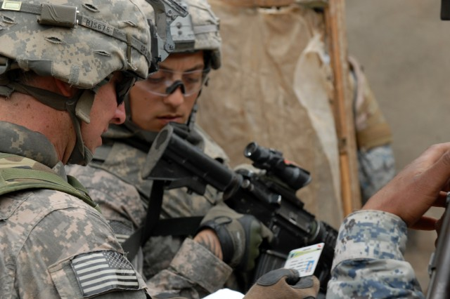 BAGHDAD - Spc. Michael Ingles (forground), a native of Royce City, Texas and Spc. Martin Aguilar, from Downey, Calif., both cannon crewmembers assigned to Battery B, 1st Battalion, 319th Airborne Field Artillery Regiment, check a man's identification card during Operation Bull Chisel March 30.