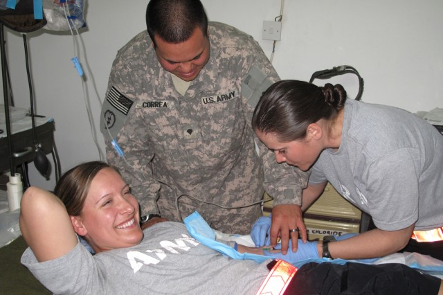 Capt. Jennifer Nihill (right) administers an IV to 1st Lt. Kim Jones as part of Officer Professional Development Training at FOB Bernstein March 20 as medic Spc. Michael Correa supervises her.