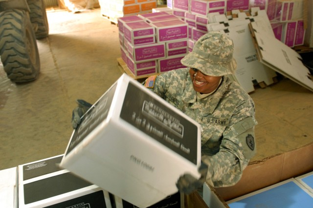 Pvt. Temira Dunn, a supply specialist with Headquarters Company, 325th Brigade Support Battalion, 3rd Infantry Brigade Combat Team, 25th Infantry Division, places a box of books into a pallet March 28. The books will to be delivered to Iraqi schools throughout the Salah ad-Din province.