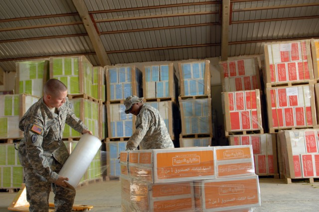 Pvt. 1st Class Aaron Boatright, a supply specialist with Headquarters Company, 3rd Infantry Brigade Combat Team, 25th Infantry Division, and Pvt. Temira Dunn, also a supply specialist with headquarters company, wrap a pallet of books March 28. The books will be delivered to Iraqi school children throughout the Salah ad-Din province.