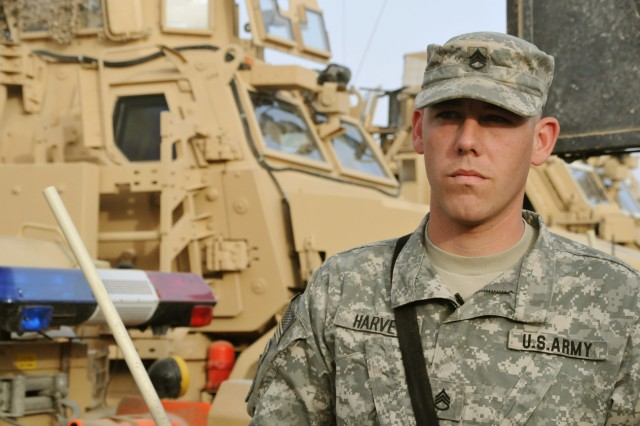 Staff Sgt. Matthew Harvey, construction supervisor with Co. E, 2nd Combined Arms Bn., 8th Inf. Regt., 2nd BCT, 4th Inf. Div., stands in front of his vehicle March 20 at Camp Echo. The vehicle was the same one he was next to when he was shot Feb. 10 during a route clearance mission in Najaf.