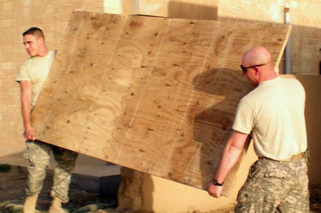"Spc. James Blanton (left) , heavy wheeled vehicle operator, 70th Trans. Co., 391st Combat Sustainment Support Battalion, and Sgt. John Deeds, armorer, 70th Transportation Co., work together to carry a piece of plywood into their new company command post to build a wall that will section off offices. The Mannheim, Germany-based Soldiers of the 70th Trans. Co., 391st CSSB, 16th Sust. Bde., were recently moved to a new area for the fourth time in their deployment, but they enjoy the challenge. ""I like to look at a job and see something I did,"" Blanton said. ""I look at these buildings and think that I helped do this.  The progress we have made is definitely the best thing to see."""
