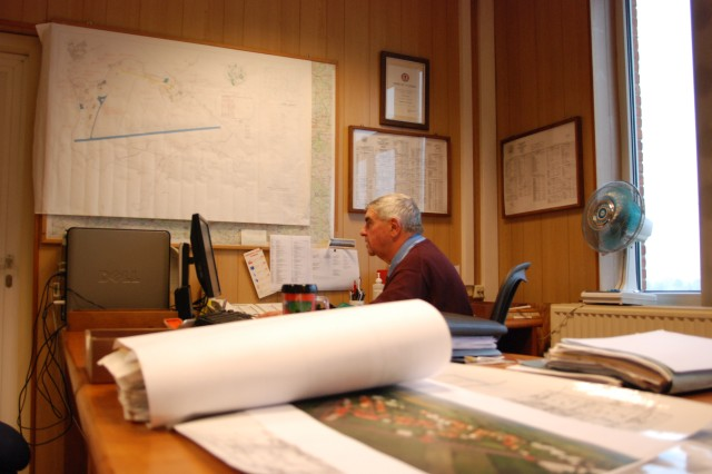 As the Technical Director of Public Works for the USAG Benelux, JP Hindricq, a Belgian employee, is surrounded by plans and maps that are the foundations of the garrisons.