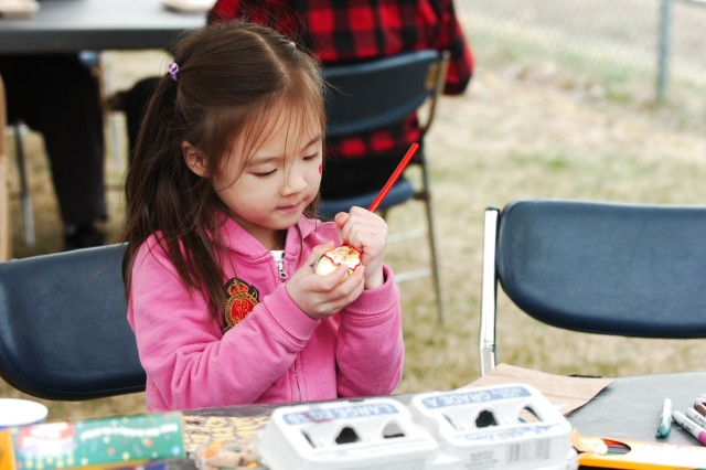 Christine Kim, age 6, the daughter of 2nd Lt. Sae Kim, the Biological Integrated Detection Systems Platoon Leader for 4th Chemical Co, 1st Brigade Special Troops Battalion, concentrates on coloring her egg at the 1st Heavy Brigade Combat Team Family Day April 3 at Camp Casey's Soldier Field.