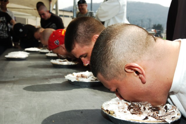 Battalion representatives from the 1st Heavy Brigade Combat Team test their resolve in a one minute pie eating contest at the 1HBCT Family Day April 3 at Camp Casey's Soldier Field.