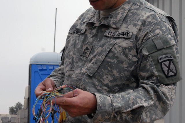 Master Sgt. Rob Schoon, 10th Mountain Division Automation Management Office noncommissioned officer-in-charge, inspects fiber optic cables that run throughout Basra Contingency Operating Base to see what can be reused.