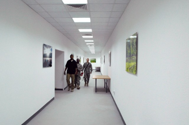 "Servicemembers walk down the hallways of one of the newly-constructed Multi-National DivisionAca,!""South headquarters buildings in Basra, Iraq. The two new buildings are nearing completion and will accommodate about 1,100 Soldiers and civilians."