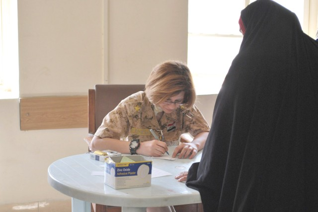 BAGHDAD - An Iraqi Army doctor writes down medical information for an Iraqi woman during a combined humanitarian mission April 1 in the al-Fadhil neighborhood of eastern Baghdad. Paratroopers assigned to 5th Squadron, 73rd Cavalry Regiment, 3rd Brigade Combat Team, 82nd Airborne Division, Multi-National Division -Baghdad, partnered with their Iraqi counterparts to assist hundreds of Iraqi citizens to get free medical evaluations and an assortment of much-needed food during the mission.