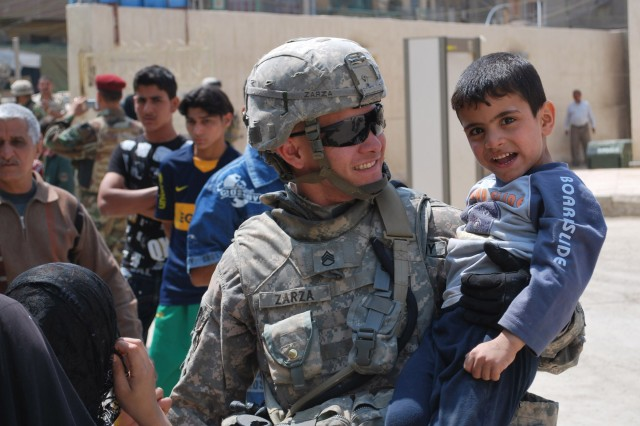 BAGHDAD - Staff Sgt. Arnold Zarza, of Mibui, Fla., carries an Iraqi boy during a combined humanitarian mission April 1 in the al-Fadhil neighborhood of eastern Baghdad. Paratroopers assigned to 5th Squadron, 73rd Cavalry Regiment, 3rd Brigade Combat Team, 82nd Airborne Division, Multi-National Division - Baghdad, partnered with their Iraqi counterparts to assist hundreds of Iraqi citizens to get free medical evaluations and an assortment of much-needed food.