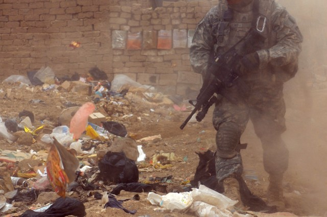 BAGHDAD - Staff Sgt. Roberto Moreno, a cannon crewmember, assigned to Battery B, 1st Battalion, 319th Airborne Field Artillery Regiment, patrols a dusty and trash-filled street in Zafaraniyah, Iraq, March 30. Moreno and his fellow paratroopers searched houses for weapons caches during an operation.