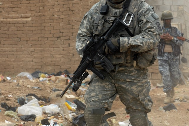 BAGHDAD - Staff Sgt. Roberto Moreno, a cannon crewmember, assigned to Battery B, 1st Battalion, 319th Airborne Field Artillery Regiment, leads an Iraqi National Policeman through a trash-lined alley during a joint operation. The operation was NP lead and they were successful in removing 21 unregistered weapons from a neighborhood in Zafaraniyah, Iraq, March 30.