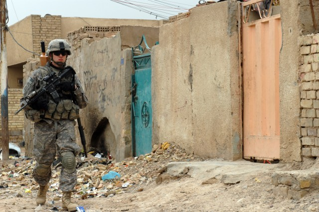 BAGHDAD - Sgt. Brandon Fellers, a native of Fort Dodge, Iowa, and a cannon crewmember assigned to Battery B, 1st Battalion, 319th Airborne Field Artillery Regiment, patrols a neighborhood in Zafaraniyah, Iraq, March 30 during a joint operation. Fellers and his fellow paratroopers worked closely with the Iraqi National Police to accomplish the mission quickly and without incident.
