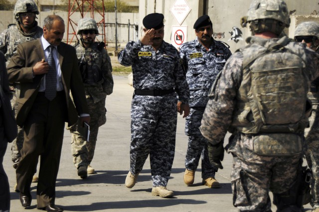 BAGHDAD - Qais Shathir Khemis Al-Jabouri, a Sheik from the Mada'Qada (left) walks with Brig. Gen. Emad  Abd Ali, commander, 3rd Brigade, 1st National Police Division,(center) and Col. Ehsan Ali Jassim, commander, 2nd Battalion, 3rd Brigade, 1st NP Div., (right) shortly after arriving at Freedom Rest via helicopter for the Mada'in Qada Farewell Luncheon, hosted by the 2nd Brigade Combat Team, 1st Armored Division, Multi-National Division - Baghdad, April 1. The Iron Brigade officially handed over the Mada'in Qada, southeast of Baghdad after 11 months of operations to the 3rd Brigade Combat Team, 82nd Airborne March 31.