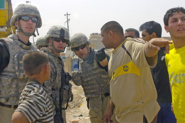 SHAWRA WA UM JIDIR, Iraq - A Iraqi man talks to members of the embedded provincial reconstruction and Lt. Col. Michael Shinners, deputy brigade commander of the 3rd Brigade Combat Team, 82nd Airborne Division, Multi-National Division - Baghdad, during a foot patrol inside a market April 4 in the city of Shawra Wa Um Jidir, located in the 9 Nissan district of eastern Baghdad. The visit was in order to evaluate the current construction projects in the area. The projects will help to improve the city's economy, quality of life and create jobs for the residents in the poverty stricken region.