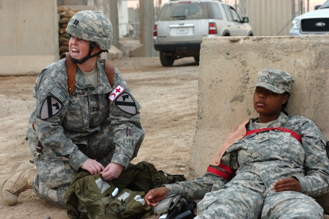 CAMP LIBERTY, Iraq - Killeen, Texas native, Capt. Kimberly Latham (left), a physician's assistant, Division Special Troops Battalion, 1st Cavalry Division, shouts out orders to medics and other Soldiers involved in a mass casualty exercise as she prepares to treat the wound of Fort Wayne, Ind. native, Pfc. Ashley Callines of Company A, DSTB, who acts as a simulated casualty.