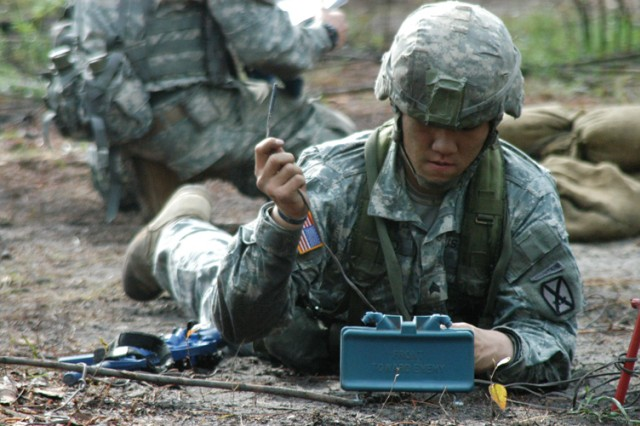 A Soldier of the 4th Brigade Combat Team, 10th Mountain Division, emplaces a claymore mine during Expert Infantryman Badge testing March 25.