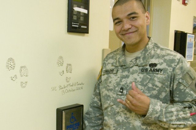 SCHOFIELD BARRACKS, Hawaii - Sgt. 1st Class Gabriel Camacho, Warrior Transition Unit, poses next to his signature on the wall of the Warrior Transition Clinic (WTC). With each signature, Soldiers leave a story and example behind, graduating from the WTC and aiding other transitioning Soldiers in their quest to complete treatment.