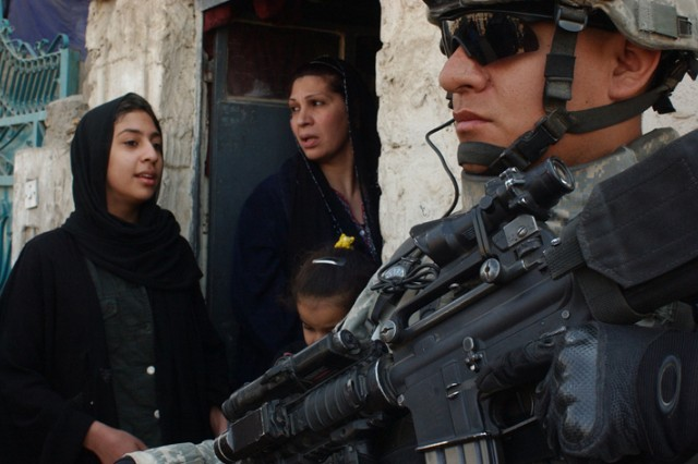 Cpl. Joseph Casiano pulls security during a combined cordon and search with the Iraqi National Police in the Ur area of Baghdad. Casiano is from Black Hawk Company, 1st Battalion, 23rd Infantry Regiment, 3rd Brigade Combat Team, 2nd Infantry Division.