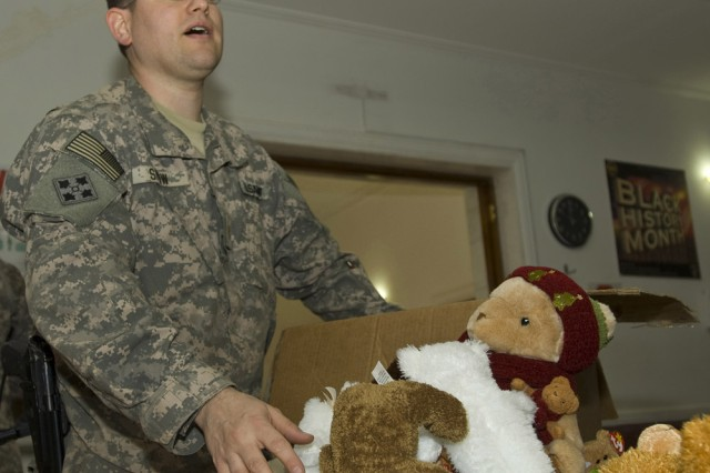 Maj. Marcus Snow, economic development officer for the 304th Civil Affairs Brigade, unpacks a box of toys from his hometown of Philadelphia in anticipation of the arrival of children from the Iraq National Institute of Handicapped Orphans on March 3. These civil affairs Soldiers volunteer their time and energy to spend an afternoon with the children distributing clothes and toys. This unit has participated twice before with this orphanage and has collected and distributed several thousands of dollars worth of winter clothes, shoes, educational material and toys. Donations come from family members and caring donors back in the Philadelphia area. All of these Reserve Soldiers say that when they return back home they plan on spreading the word to collect material for these less fortunate children in Baghdad. This Army Reserve brigade, composed of Warrior Citizen Soldiers from the Philadelphia area, are part of the U.S. Army Civil Affairs and Psychological Operations Command (Airborne), headquartered at Fort Bragg, N.C. ""