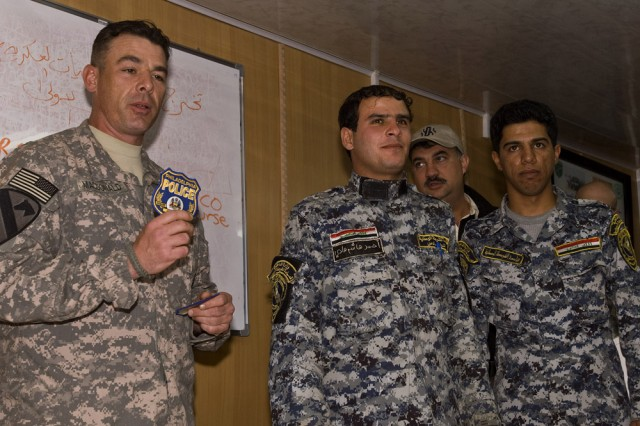 Sgt. 1st Class Daniel P. MacDonald, the chief non-commissioned officer instructor, and a police captain in the 12th District with the Philadelphia Police Department, presents his department's police patch to two Iraqi national police officers at the graduation ceremony. He said he hopes for a long-term friendship and collaborative relationship between the Iraqi police and the departments around the world. The Iraqi police force is set up as a paramilitary state police force, much like the Italian Arma dei Carabinieri. MacDonald, along with Lt. Col Charles Anderson, a fellow Army Reserve member of the 304th Civil Affairs Brigade, were both instrumental in developing the Civil Military Operations course for the Iraqi army. This Army Reserve brigade, composed of Warrior Citizen Soldiers from the Philadelphia area, are part of the U.S. Army Civil Affairs and Psychological Operations Command (Airborne), headquartered at Fort Bragg, N.C.""