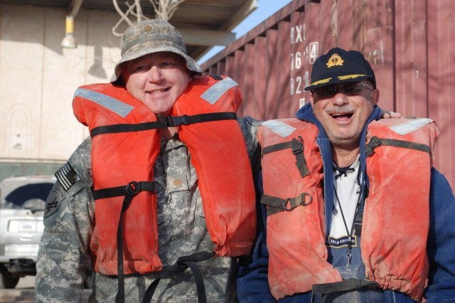 Maj. Douglas B. Bathe (left), the Agricultural officer for the Multi-National Coalition - Iraq C9, and Mr. Feras M. Chabik, a Chief Fishery biologist working for the government of Iraq, take some time to pose for the camera before their fishing mission near the Al Faw Palace on Feb. 27. Bathe, an independent farmer by trade, is an Army Reserve officer originally assigned to the 351st Civil Affairs Command out of Mountain View, Calif. He hails from the town of Arroyo Grande in San Luis Opispo County, Calif. The Multi-National Coalition - Iraq and its C9 Agriculture section is collaborating with the Iraqi government, and with some assistance from the 304th Civil Affairs Brigade, to repopulate three specific species of fish to the southeastern marshes of Iraq. The species are the Shaboot, Bunny, and Kattan (pronounced: Sha-boot, Buun-nee, and Kat-tan). One of the few places where these 3 species are found in abundance is in and around the lake complex of the Al Faw palace on Camp Victory, Iraq. The fish are being kept at Al Suwaira in the Wasit province, once the eggs hatch and become fingerlings of about 3 inches or so, they will be transferred to the marshes. The 304th Civil Affairs Brigade and the 351st Civil Affairs Command are a part of the U.S. Army Civil Affairs and Psychological Operations Command (Airborne), headquartered at Fort Bragg, N.C.""