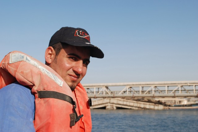 Mr. Abdezahara, a fisherman working for the government of Iraq, takes a break from rowing to smile for the camera before starting to fish near the Al Faw Palace on Feb. 27. The Multi-National Coalition - Iraq and its C9 Agriculture section is collaborating with the Iraqi government, and with some assistance from the 304th Civil Affairs Brigade, to repopulate three specific species of fish to the southeastern marshes of Iraq. The species are the Shaboot, Bunny, and Kattan (pronounced: Sha-boot, Buun-nee, and Kat-tan). One of the few places where these 3 species are found in abundance is in and around the lake complex of the Al Faw palace on Camp Victory, Iraq. The fish are being kept at Al Suwaira in the Wasit province, once the eggs hatch and become fingerlings of about 3 inches or so, they will be transferred to the marshes. The 304th Civil Affairs Brigade is a part of the U.S. Army Civil Affairs and Psychological Operations Command (Airborne), headquartered at Fort Bragg, N.C.""