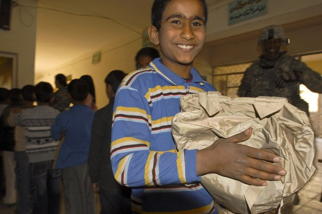This Iraqi boy is beaming as he carries his brand new backpack donated as part of a comprehensive educational program by the Wasit Provincial Reconstruction Team at Al Kut on March 5. Elements of the 304th Civil Affairs Brigade are working closely with the local PRT to provide needed infrastructure and professional assessments of area schools and to distribute collected items. These Provincial Reconstruction Teams are spearheaded by the Department of State with support from civil affairs personnel, and are designed to empower the local Iraqi private and public sectors. The 304th Civil Affairs Brigade is an Army Reserve brigade, composed of Warrior Citizen Soldiers from the Philadelphia area, and are part of the U.S. Army Civil Affairs and Psychological Operations Command (Airborne), headquartered at Fort Bragg, N.C. ""