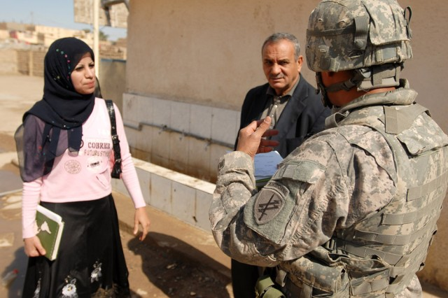 Sgt. Ivan Cabrera, with the 490th Civil Affairs Battalion, Charlie Company, talks to Iraqi interpreter Yousrha (left) and to Abid Al Hassan Shamkhi (center), the principal of the Alistikrar primary school for boys in Al Kut on March 5. The Reserve Soldier out of Dallas, Texas, is interviewing the staff as he conducts an area assessment for the Wasit Provincial Reconstruction Team. The Wasit PRT is somewhat unique in that it has an active participation by civil affairs Soldiers from the 304th Civil Affairs Brigade and the 490th Civil Affairs Battalion, assigned to help conduct thorough area assessments to provide needed infrastructure and professional feedback to the area Provincial Reconstruction Team. These teams are spearheaded by the Department of State with support from civil affairs personnel, and are designed to empower the local Iraqi private and public sectors. Both the 304th Civil Affairs Brigade and the 490th Civil Affairs Battalion are part of the Army Reserve and are under the U.S. Army Civil Affairs and Psychological Operations Command (Airborne), headquartered at Fort Bragg, N.C. ""