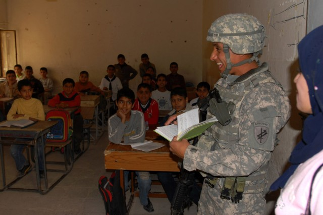 Sgt. Ivan Cabrera, with the 490th Civil Affairs Battalion, Charlie Company, talks to the teacher of a class of Iraqi boys from the Alistikrar Primary School, in Al Kut on March 5, as Iraqi interpreter Yousrha (right) watches. Cabrera, a Reserve Soldier out of Dallas, is interviewing the staff to conduct an area assessment for the Wasit Provincial Reconstruction Team. The Wasit PRT is somewhat unique in that it has an active participation by civil affairs Soldiers from the 304th Civil Affairs Brigade and the 490th Civil Affairs Battalion, assigned to help conduct thorough area assessments to provide needed infrastructure and professional feedback to the area Provincial Reconstruction Team. These teams are spearheaded by the Department of State with support from civil affairs personnel, and are designed to empower the local Iraqi private and public sectors. Both the 304th Civil Affairs Brigade and the 490th Civil Affairs Battalion are part of the Army Reserve and are under the U.S. Army Civil Affairs and Psychological Operations Command (Airborne), headquartered at Fort Bragg, N.C. ""
