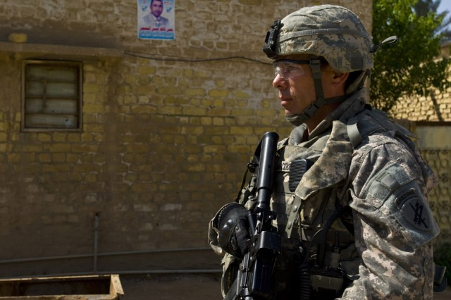 Army Reserve Soldiers with the 304th Civil Affairs Brigade patrol the streets of Mahawil, a city southwest of Baghdad, Iraq, on March 18. Sgt. 1st Class Daniel MacDonald, the non-commissioned officer in charge of the brigade's personal security detail scans the local market for any possible threats. MacDonald is police captain with the Philadelphia Police Department. This Army Reserve brigade, is composed of Warrior Citizen Soldiers from the Philadelphia area, and are part of the U.S. Army Civil Affairs and Psychological Operations Command (Airborne), headquartered at Fort Bragg, N.C.""