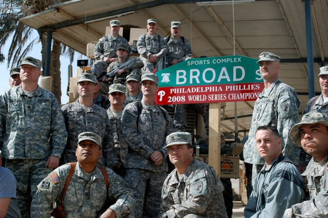 These Army Reserve Soldiers with the 304th Civil Affairs Brigade all have one thing in common, they are all die hard Philadelphia Phillies fans. The brigade, along with its true-blue fans helped coordinate the project to have one of Camp Slayer's streets renamed to honor their team. The goal was to boost moral for the Philadelphia based unit, and more importantly to remind everyone in the Baghdad region just who won the World Series. This Army Reserve brigade which is composed of Warrior Citizen Soldiers from the Philadelphia area, are part of the U.S. Army Civil Affairs and Psychological Operations Command (Airborne), headquarter at Fort Bragg, N.C.""