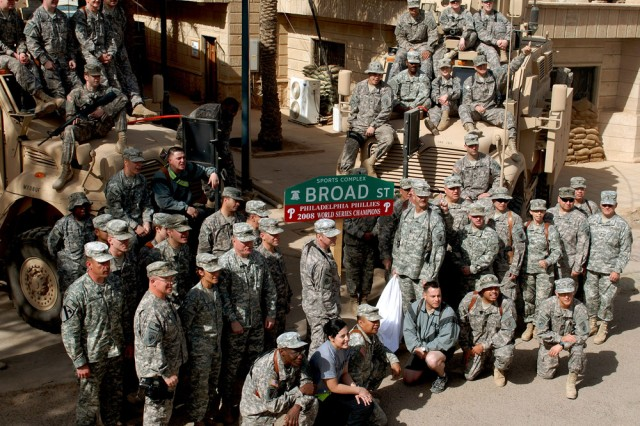 These Army Reserve Soldiers with the 304th Civil Affairs Brigade all have one thing in common, they are all die hard Philadelphia Phillies fans. The brigade, along with its true-blue fans helped coordinate the project to have one of Camp Slayer's streets renamed to honor their team. The goal was to boost moral for the Philadelphia based unit, and more importantly to remind everyone in the Baghdad region where the World Series Champions come from. This Army Reserve brigade which is composed of Warrior Citizen Soldiers from the Philadelphia area, are part of the U.S. Army Civil Affairs and Psychological Operations Command (Airborne), headquarter at Fort Bragg, N.C""