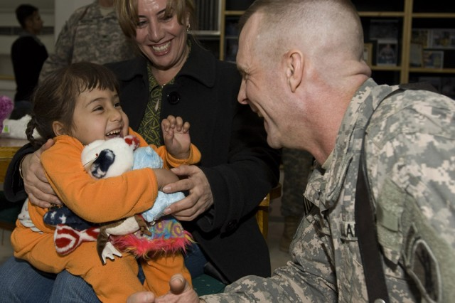 "Col. Charles ""Chuck"" Wogan, deputy commanding officer for the 304th Civil Affairs Brigade, clowns around with little Huda and makes her smile as Dr. Suzan Karim, a bilingual and bi-cultural advisor to the brigade looks on. Little Huda, 5 years old, is one of the many handicapped children who is both an orphan and severely disabled. Wogan, who works as a Philadelphia based IRS criminal tax attorney on his civilian side, says these events have been highlight of his tour. The 304th Civil Affairs Brigade does not have as its mandate to help orphanages, but its Reserve Soldiers from Philadelphia certainly do. Wogan's boss, Linda S. Bednarz, chief counsel for the IRS in Philadelphia, has been a key organizer stateside for collecting thousands of dollars worth of clothes, toys and school supplies for these less fortunate children. This Army Reserve brigade which is composed predominantly of Warrior Citizen Soldiers from the Philadelphia area, is part of the U.S. Army Civil Affairs and Psychological Operations Command (Airborne), headquartered at Fort Bragg, N.C."""
