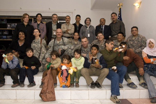 A group shot of the children, the Iraqi volunteers and institute workers, along with the volunteer Army Reserve Soldiers of the 304th Civil Affairs Brigade. The civil affairs brigade does not have as its mandate to help orphanages, but its Reserve Soldiers from Philadelphia certainly do. All of these Reserve Soldiers say that when they return back home they plan on spreading the word to collect material for these less fortunate children in Baghdad. This Army Reserve brigade which is composed predominantly of Warrior Citizen Soldiers from the Philadelphia area, is part of the U.S. Army Civil Affairs and Psychological Operations Command (Airborne), headquartered at Fort Bragg, N.C.""