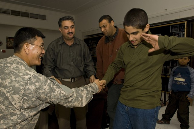 U.S. Navy Lt. Pete Bingus Tamminga takes a hardy handshake and a salute from one of the children visiting from the Iraqi National Institute of Handicapped Orphans. Tamminga is a regular U.S. Navy officer assigned to the 304th Civil Affairs Brigade as their infrastructure projects manager, where he acts as a liaison for all economic construction initiatives that the brigade supports. A naval aviator by training, he said spending time with these kids has been one of the highlights in Baghdad this past year. Originally from Bozeman, Mont., and the Lexington Park, Md., area, Tamminga will return to naval aviation at NAS Fallon after his tour in Baghdad is complete. This Army Reserve brigade is predominately composed of Warrior Citizen Soldiers from the Philadelphia area and are part of the U.S. Army Civil Affairs and Psychological Operations Command (Airborne), headquartered at Fort Bragg, N.C.""