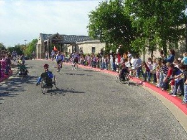 Handcrank cyclists pass by cheering crowds