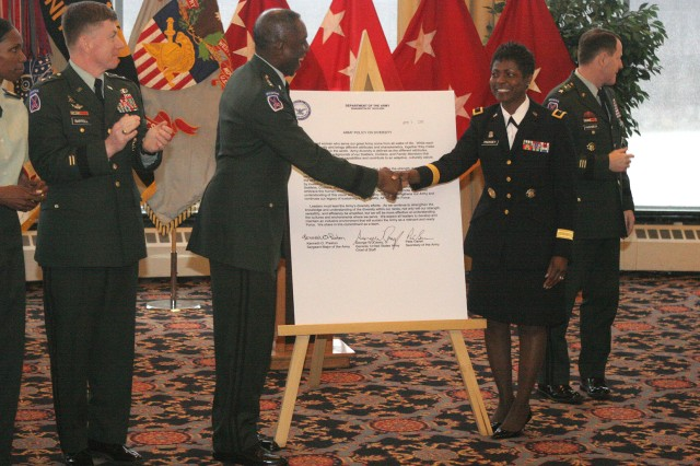 Gen. Kip Ward and Brig. Gen. Belinda Pinckney shake hands in front of the enlarged Army Diversity Policy memorandum at the West Point conference as Maj. Gen. Arthur Bartell of U.S. Army Cadet Command applauds.