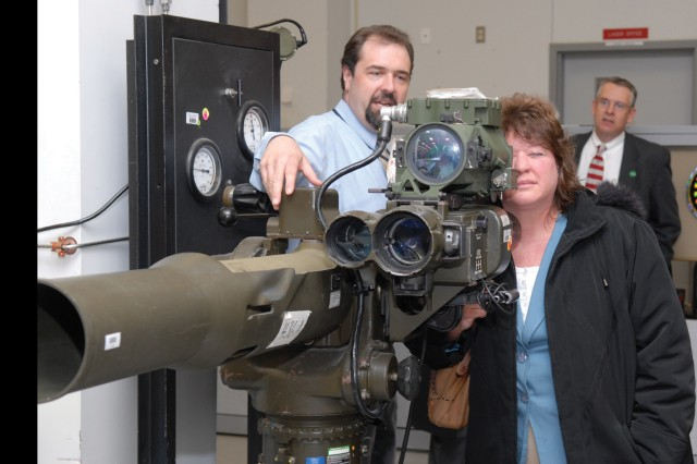 Joe Fantanarosa (left) briefs Debbie Schmidt  and Charles Barber, Northeastern Pennsylvania Alliance staff and board members, respectively, on the UAS-12C Night Sight Equipment Set.  Fantanarosa is chief of the Electro-Optic/Night Vision Division. The set is used in conjunction with the M220 tube-launched optically-tracked wire-guided (TOW) missile launcher.  During the March 25 visit, the NEPA members were briefed on the installation's operations, and toured the depot.