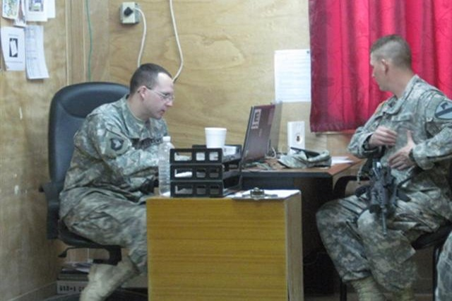 CAMP LIBERTY, Iraq -- Pfc. Daniel Easterly, a Jacksonville, Fla. native, and Soldier from Delta Detachment, 101st Financial Management Company, 10th Sustainment Brigade Troops Battalion, 10th Sustainment Brigade helps resolve Pvt. Christian Johnson's, of Durham, N.C., Eagle Cash Card problem at Camp Liberty finance office.