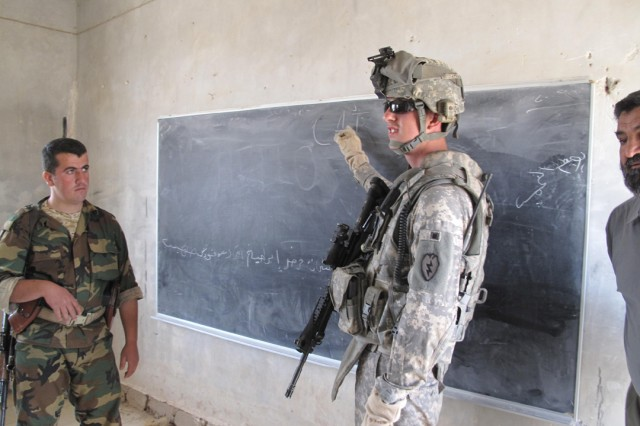 Staff Sgt. Josh Remmark of Canton, S.D., writes the word 'cat' on a chalkboard at the Banyas School in Zaggurbanya Village April 2 as Iraqi soldier Shwan Ibrahim Mowlud looks on.  Soldiers from the Special Troops Bn., 3rd Inf. Bde. Combat Team, 25th Inf. Div., are working with the Government of Iraq through the Iraqi Army to improve the school, which is now in a shambles, to make it more functional before the beginning of the next school year.