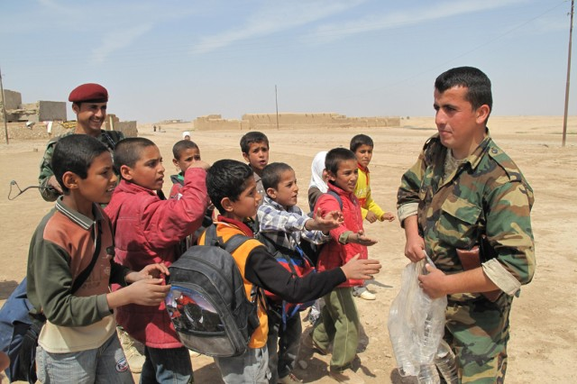 Iraqi Army soldiers Hardi Hassan Mustafa (left) and Shwan Ibrahim Mowlud give bottled water to students outside the Banyas School in Zaggurbanya Village April 2.  The Iraqi Army, with help from CF, is set to make several improvements to the local school before the beginning of the next school year.