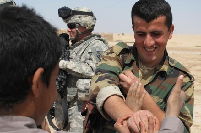 Iraqi Army Soldier Shwan Ibrahim Mowlud playfully fends off the grasping hands of Iraqi schoolchildren as he passes out candy in the Zaggurbanya Village April 2.  Soldiers from the Special Troops Bn., 3rd Inf. Bde. Combat Team, 25th Inf. Div. and soldiers from the Iraqi Army's 16th Bde. are working together in the area to improve school conditions before the beginning of the next school year.