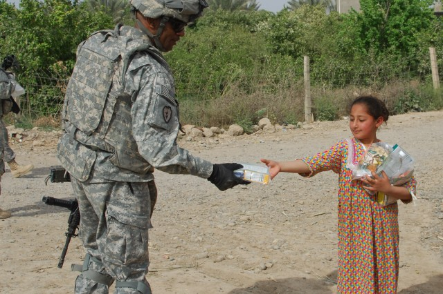 FORWARD OPERATING BASE SPEICHER, TIKRIT, Iraq - Command Sgt. Maj. Thomas Jones, battalion sergeant major, 2nd Battalion, 35th Infantry Regiment, 3rd Infantry Brigade Combat Team, 25th Infantry Division hands a package of supplies to a local girl during the battalion's delivery of dozens of humanitarian aid packages to the Bara'ia neighborhood near Samarra, March 31.